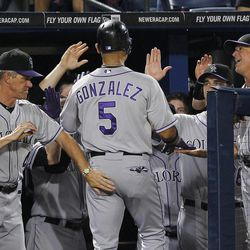 Colorado Rockies' Carlos Gonzalez (5) is greeted by manager Jim Tracy, left, and bench coach Tom Runnells (11) after hitting a solo home run in the fourth inning of a baseball game against the Atlanta Braves on Tuesday, Sept. 4, 2012, in Atlanta.