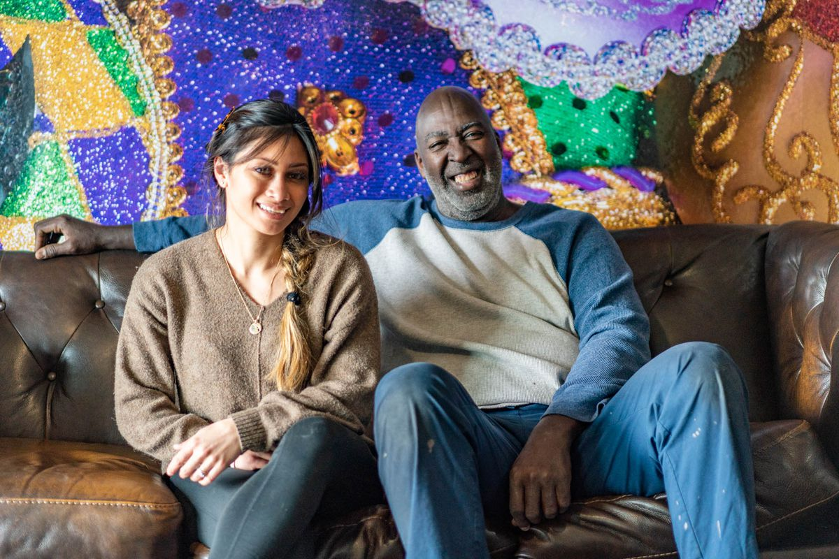 Dat Creole Soul's Angelica Carrasco and Hampton Isom sit together on a leather couch with a colorful mural behind them.