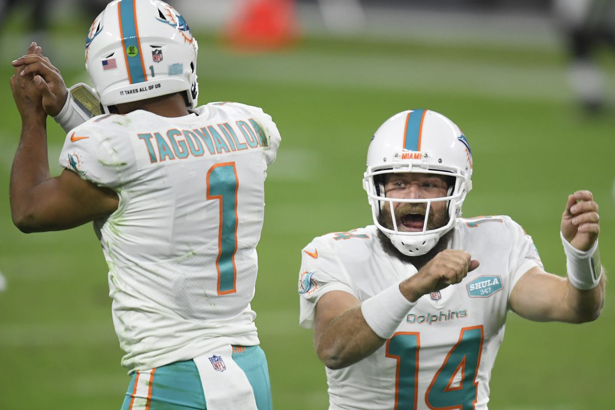 yan Fitzpatrick #14 of the Miami Dolphins celebrates his touchdown pass with Tua Tagovailoa #1, to take a 23-22 lead over the Las Vegas Raiders, during the fourth quarter at Allegiant Stadium on December 26, 2020 in Las Vegas, Nevada.