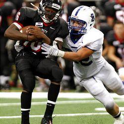 Bingham's Brandon Lambert, right, works to bring down Trinity quarterback Willie Hubbard Monday during action in the Kirk Herbstreit Varsity Football Series at Cowboys Stadium.