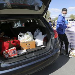 Volunteer Hayden Wilding loads a car up with food from the Utah Food Bank in the parking lot of a chapel belonging to The Church of Jesus Christ of Latter-day Saints in Taylorsville on Monday, April 13, 2020.The Utah Food Bank estimates it provided food to around 400 families at this location.