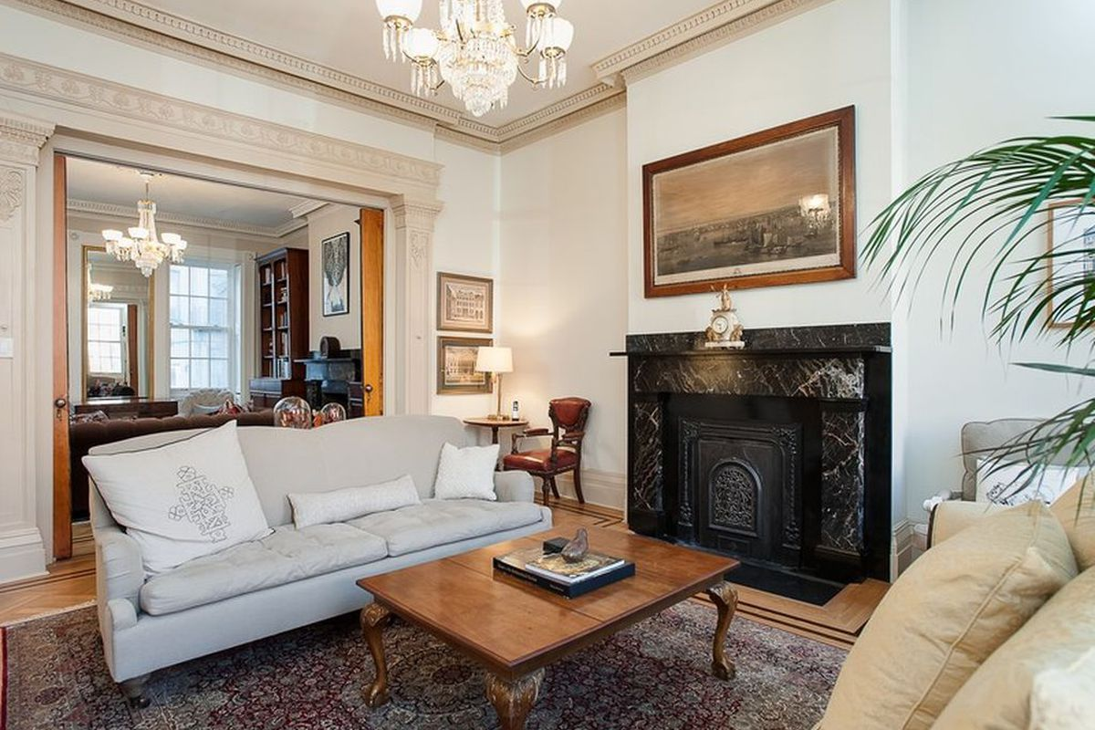 Interior shot of formal sitting room with high ceilings, crown molding, chandelier, ornate fireplace, and a view into the next room via pocket doors.