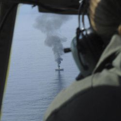 Coast Guard Petty Officer Charly Hengen, aboard a C-130, watches a  giant plume of smoke rise from a derelict Japanese ship after it was hit by canon fire by a U.S. Coast Guard cutter on Thursday, April 5, 2012, in the Gulf of Alaska. The Coast Guard decided to sink the ship dislodged by last year's tsunami because it was a threat to maritime traffic and could have an environmental impact if it grounded.