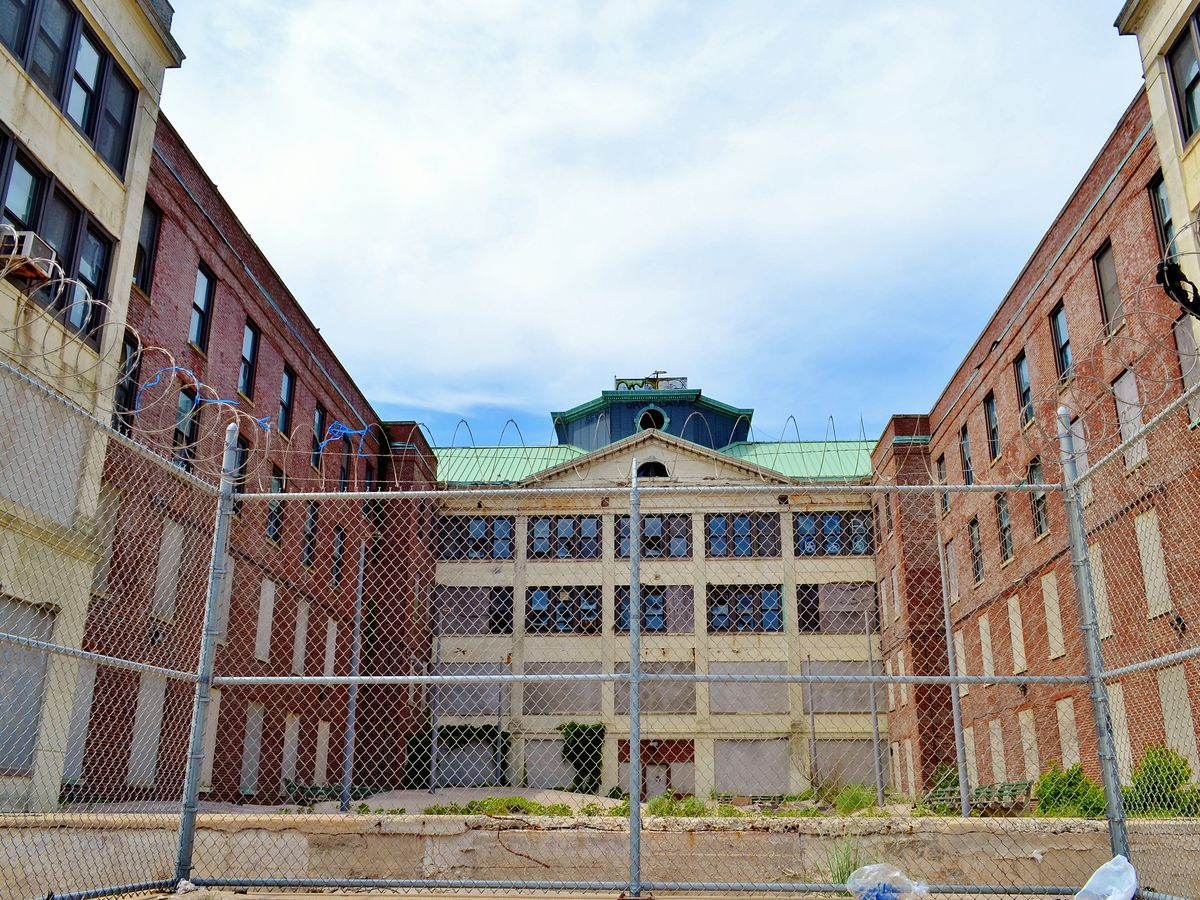 The exterior of the Neponsit Health Care Center. There is a fence with barbed wire on top in the foreground. In the background are a group of abandoned buildings with brick facades.