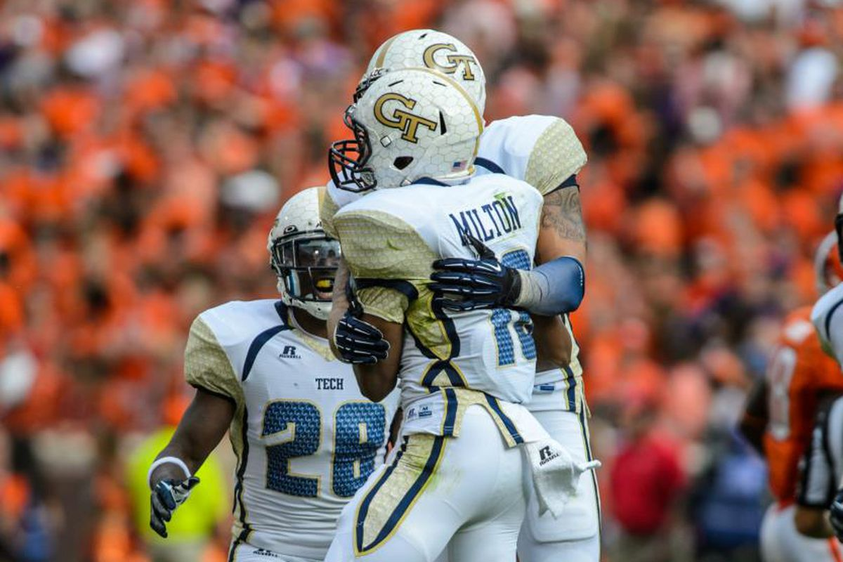 Georgia Tech defenders Chris Milton, D.J. White (#28), and Daniel Drummond celebrate after a play against the Clemson Tigers.