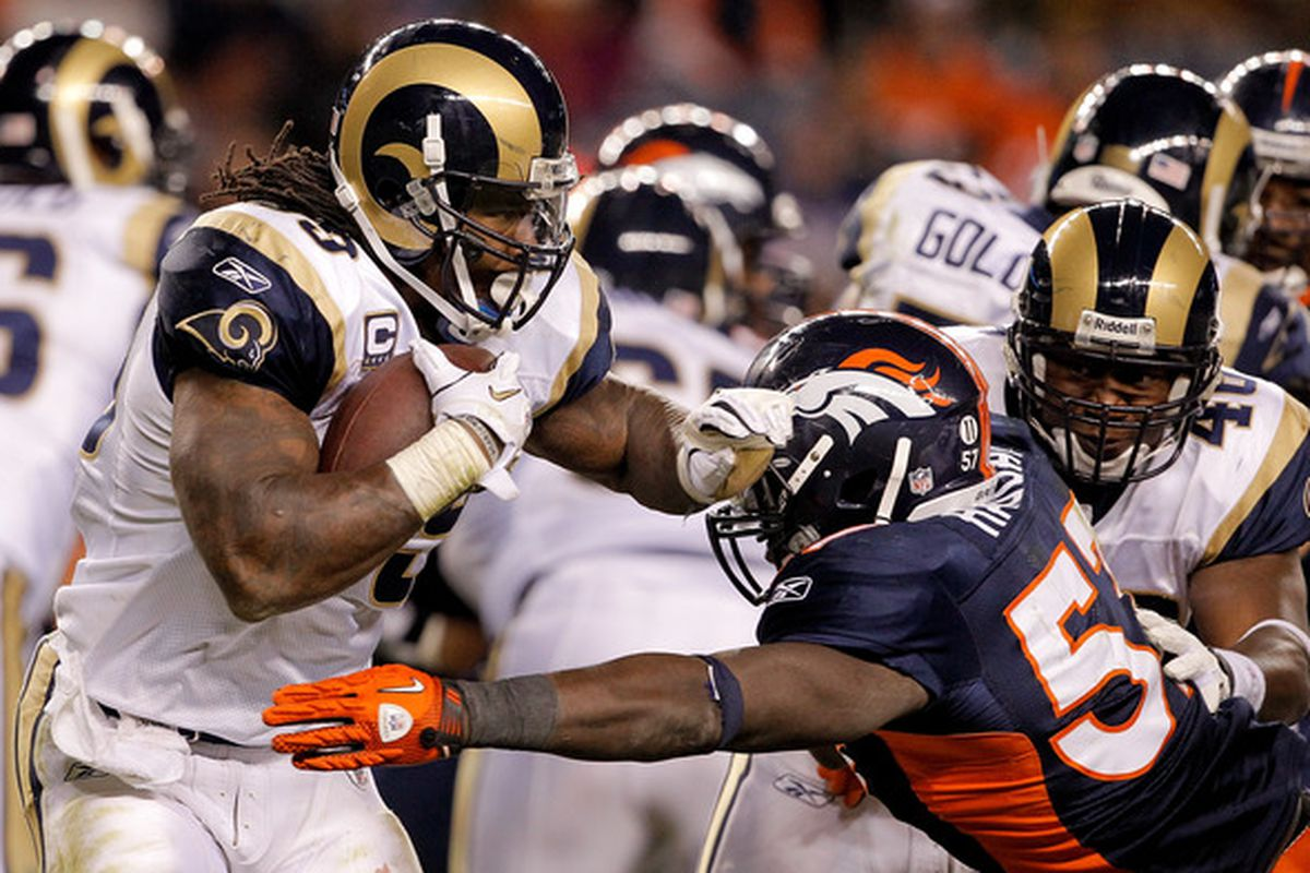 Running back Steven Jackson of the St. Louis Rams tries to break outside of linebacker Mario Haggan of the Denver Broncos during the fourth quarter.
