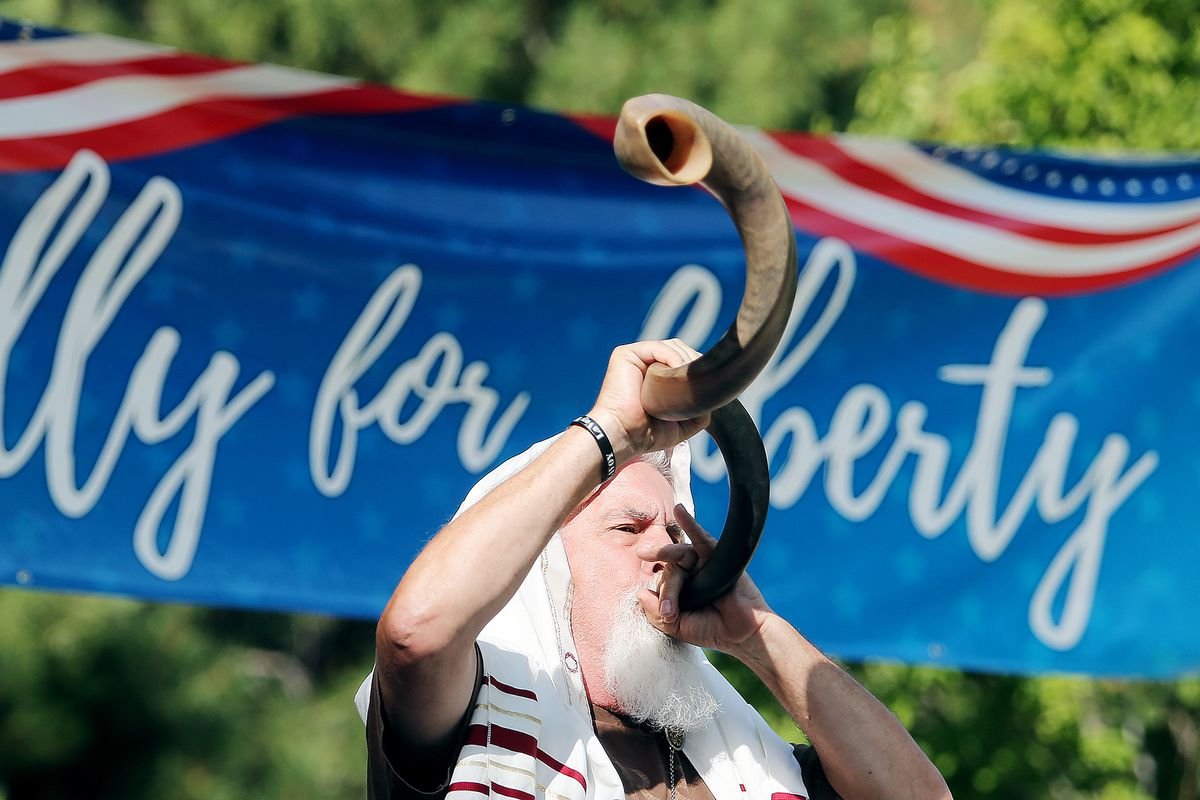 Brand Thornton blows a shofar horn as protesters gather in the City Center Park of Orem in opposition to mask mandates on Wednesday, Aug. 5, 2020.