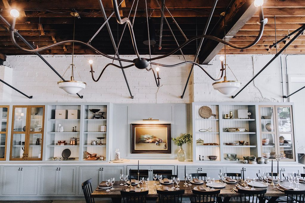 A large white room with bookshelves, exposed wood beams, and a long farmhouse table set for dinner