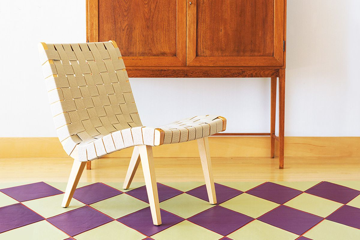 A curved lounge chair with light wood base and a basket weave of cream-colored cotton strips.