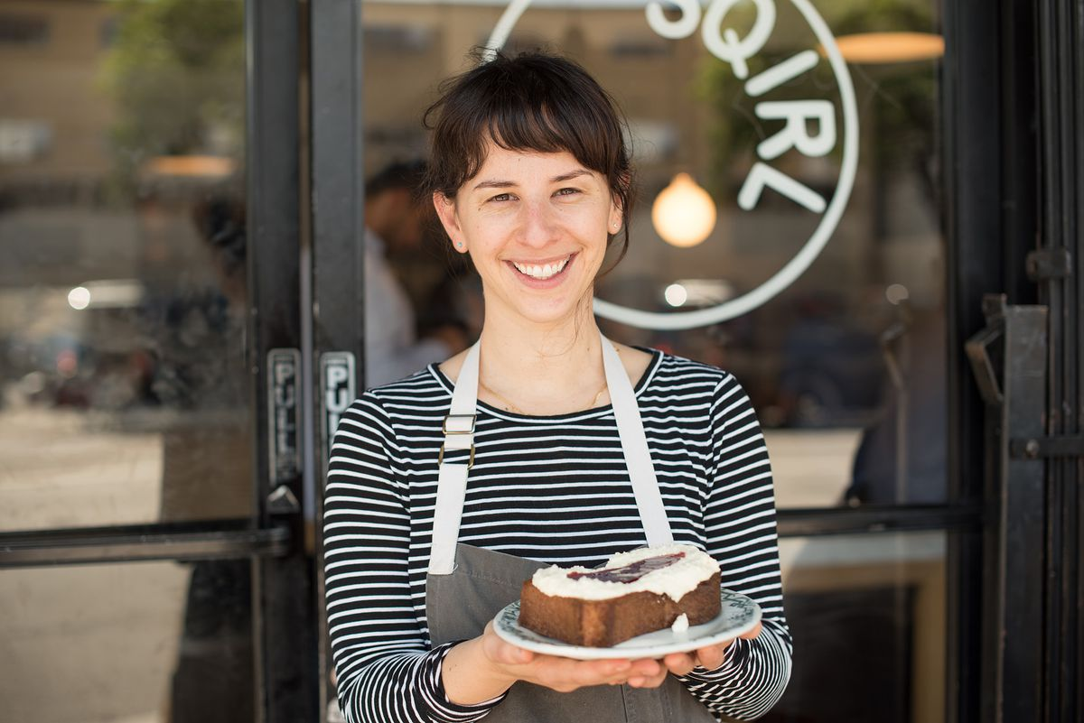 Jessica Koslow, the cehf-owner, stands at Sqirl holding a plate of toast with jam.
