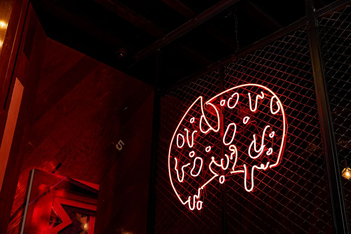 A red neon pizza sign hanging on a metal cage.