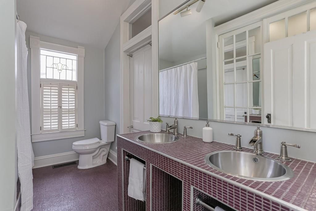 A large bathroom with purple tile and a dual vanity.