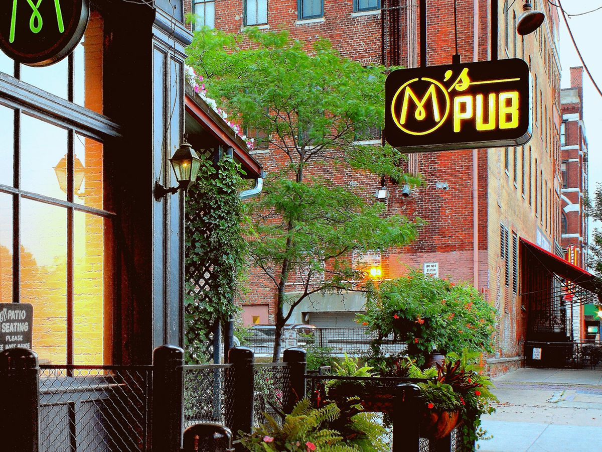 A red brick restaurant exterior with greenery and pub sign