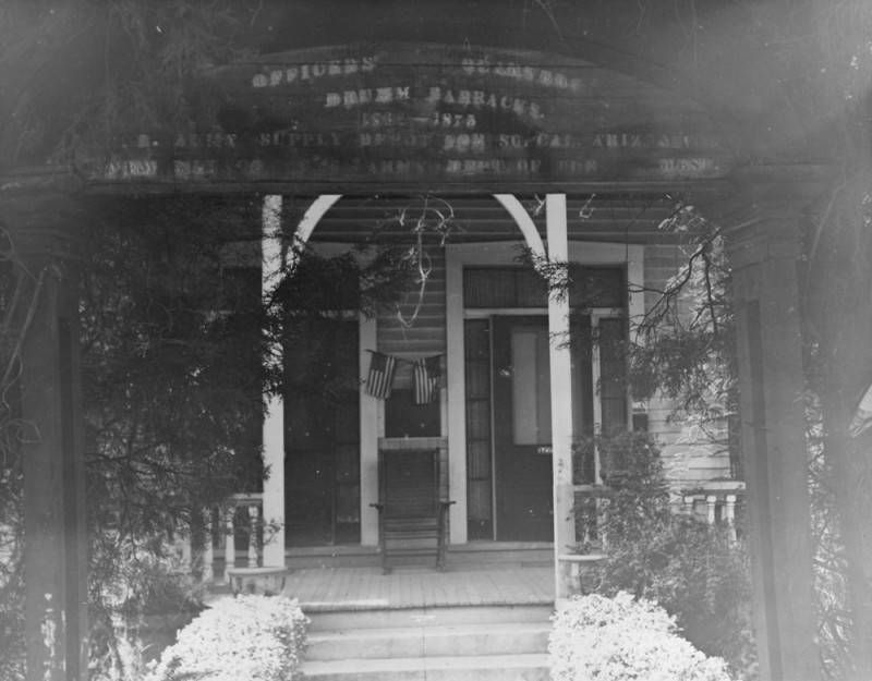 Black and white photo of the entrance of a clapboard building fronted by a wooden porch. Two small American flags are affixed to the facade.