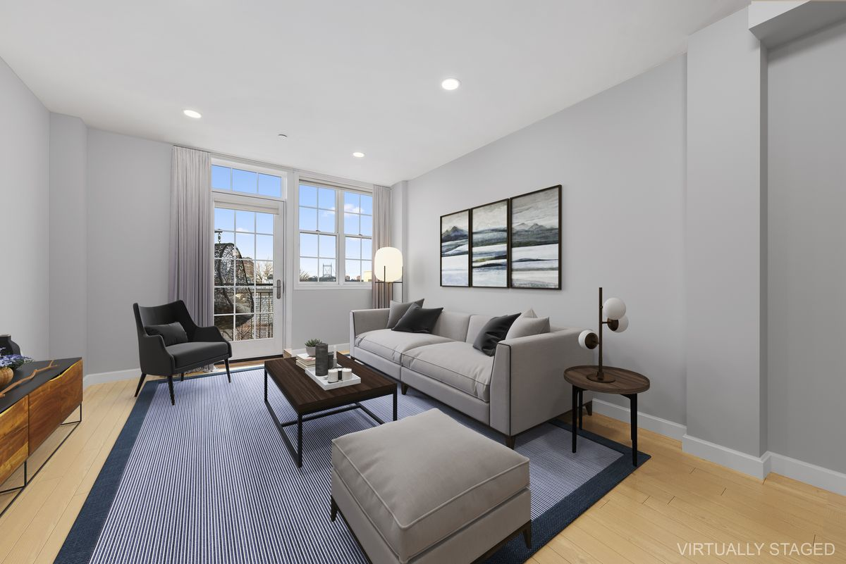 A living area with a grey couch, a blue rug, hardwood floors, and grey walls.