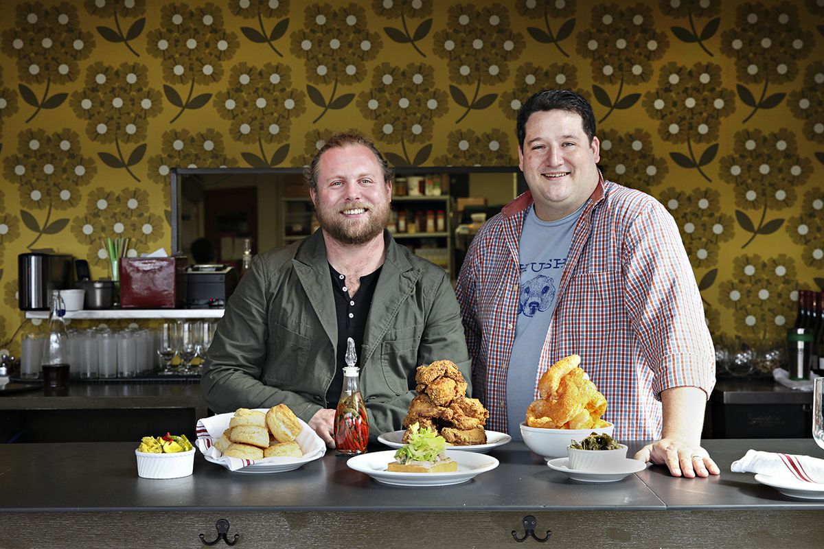 Nick Rancone is on the left, curly blonde hair in a pony tail wearing a suit jacked over a black Henley, Thomas Boemer on the right, with close cropped brown hair, a plaid shirt unbuttoned over a blue t-shirt. In front of them is a spread of Revival dishes including crispy fried chicken