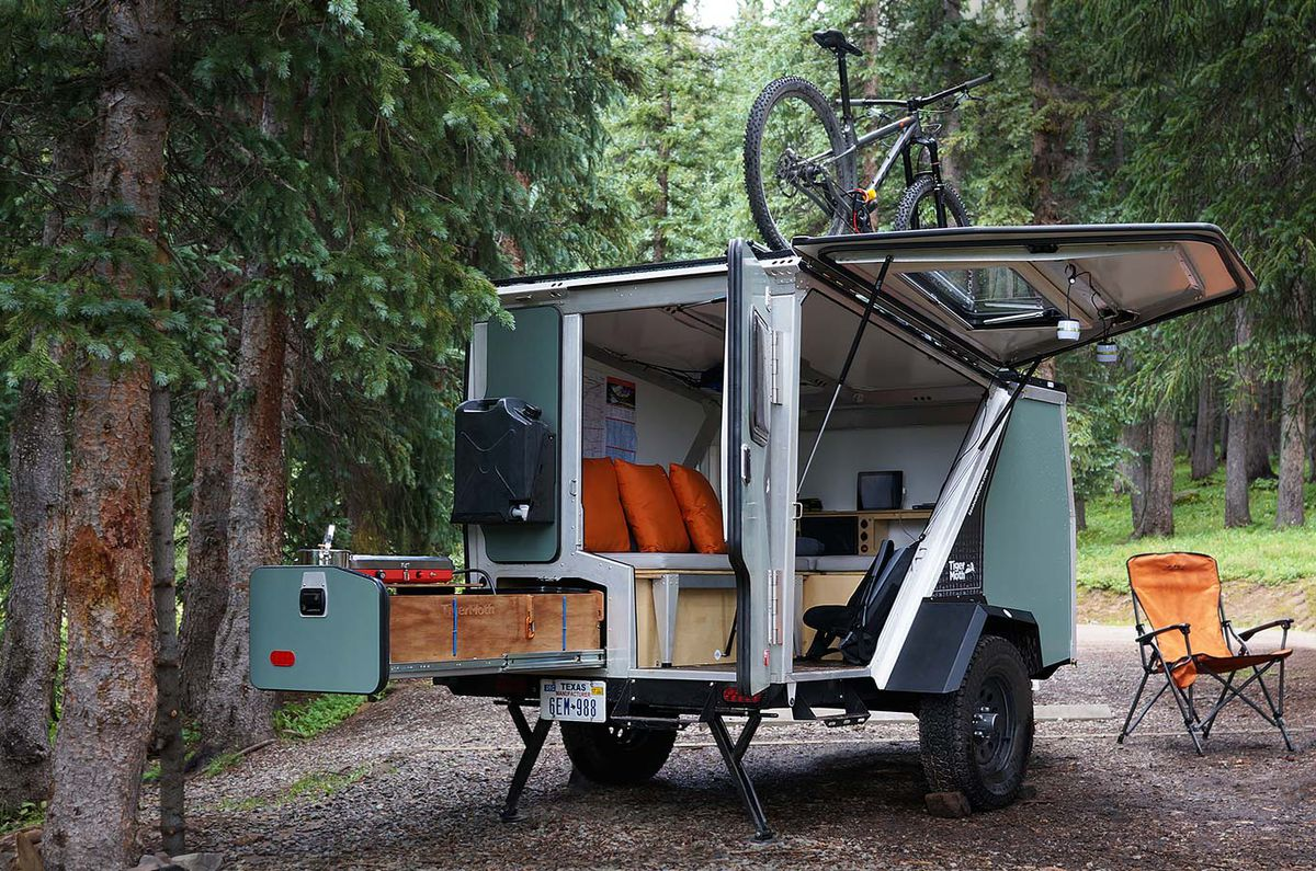 A camper van, the Tigermoth, at a campsite. The van is light blue and all of its doors are open. There is a storage compartment that slides out of the back of the van. There is a bicycle on top of the van and an orange chair sitting outside of the van.