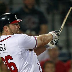 Atlanta Braves second baseman Dan Uggla (26) puts the Braves ahead with a broken-bat two-run base hit in the eighth inning of a baseball game against the Milwaukee Brewers in Atlanta, Friday, April 13, 2012.
