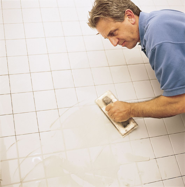 Man Applies Grout Over Tile Tub Surround