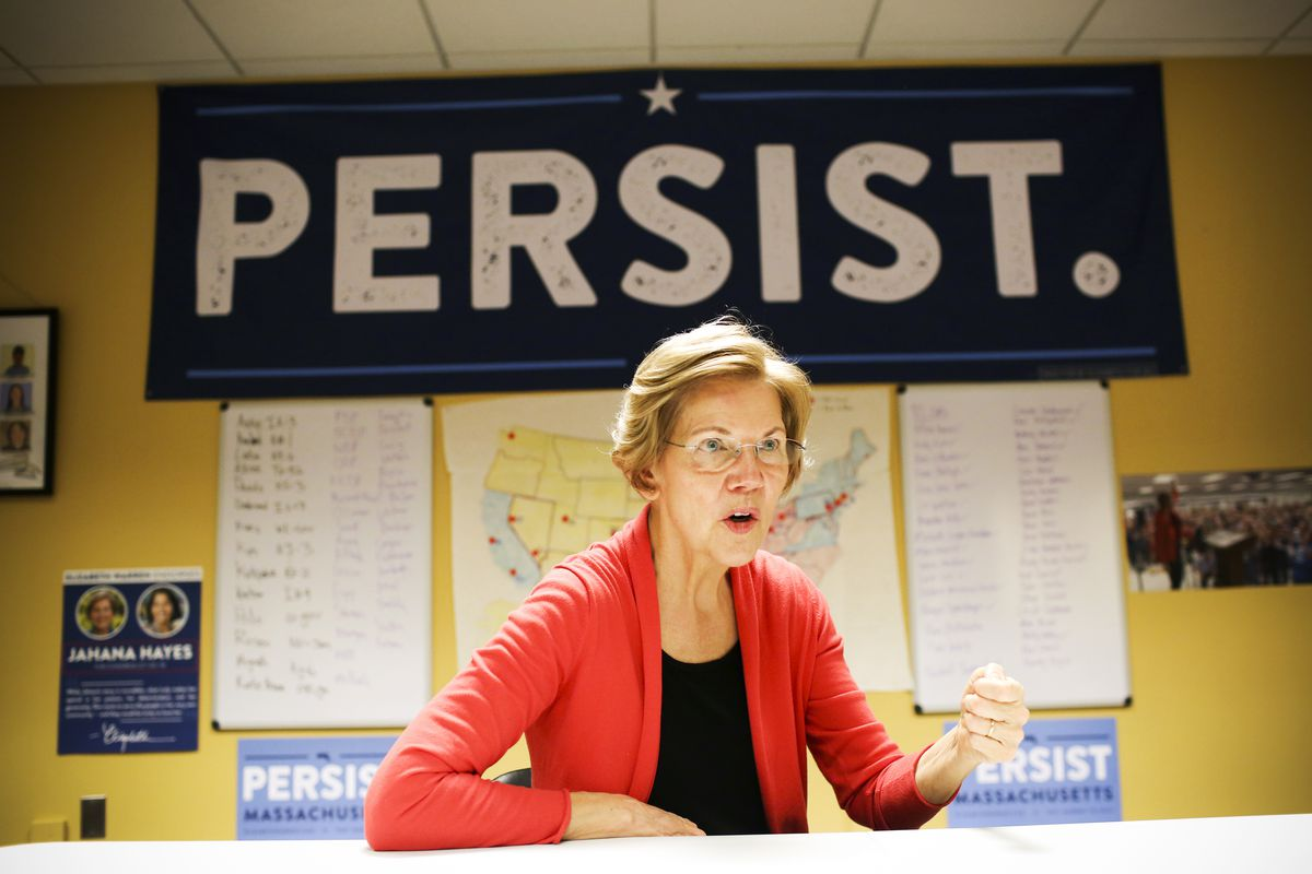 Senator Elizabeth Warren speaks in the Democratic Outreach Team's room at her campaign headquarters in Dorchester, MA on October 12, 2018. A map of competitive congressional races that the team is tracking is hung up on the wall behind her.