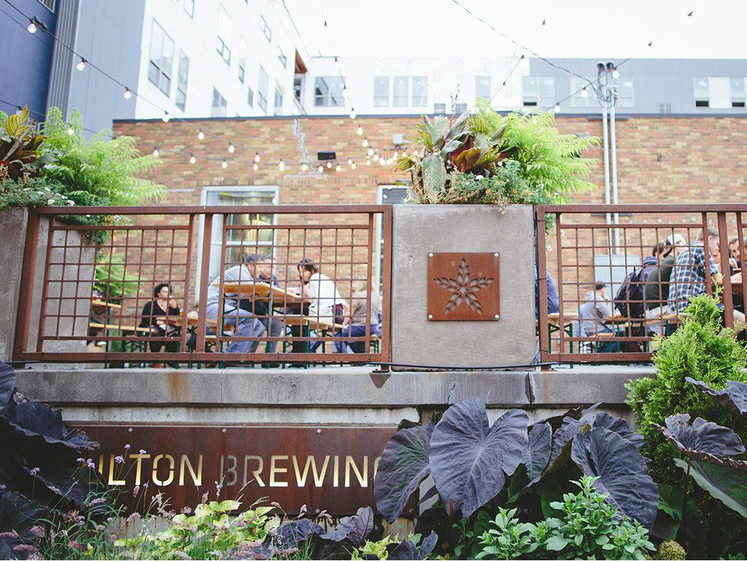 A view looking up from below at Fulton's patio with green landscaping and people drinking beer in the background