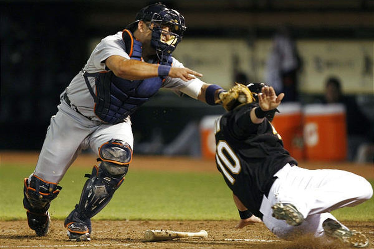 Oakland Athletics' Daric Barton right, is tagged out at the plate by Detroit Tigers catcher Gerald Laird as Barton tried to score from third base on a ground ball by Adam Kennedy during the fifth inning.