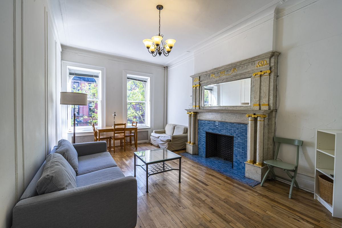 A living area with hardwood floors, base and crown moldings, two windows, white walls, a couch, and a fireplace surrounded with blue tiles.