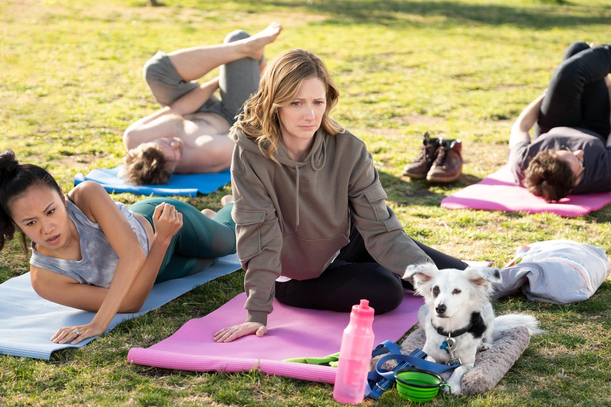 Maggie (Judy Greer) and Reuben (Chico the dog) attend a dog-friendly yoga class