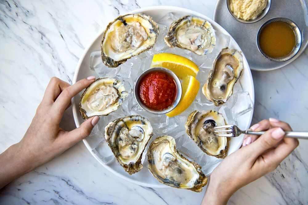A bunch of oysters on a platter with red sauce and lemon slices at the center. A hand picks up one and holds a shrimp fork in the other.