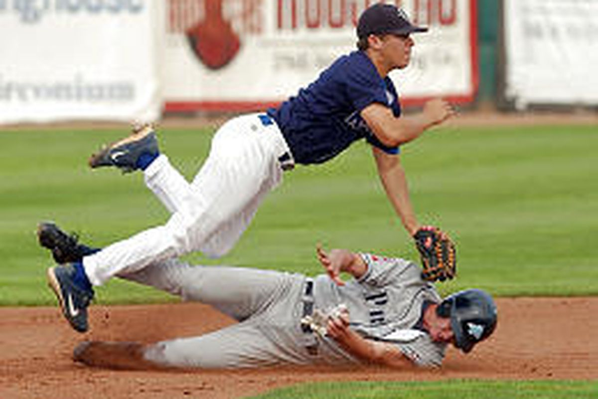 Ogden infielder Dominique Laurin dives over Matt Brown's slide into second base while throwing to complete a second-inning double play. The Provo Angels tied the Pioneer League playoff series at one game each.
