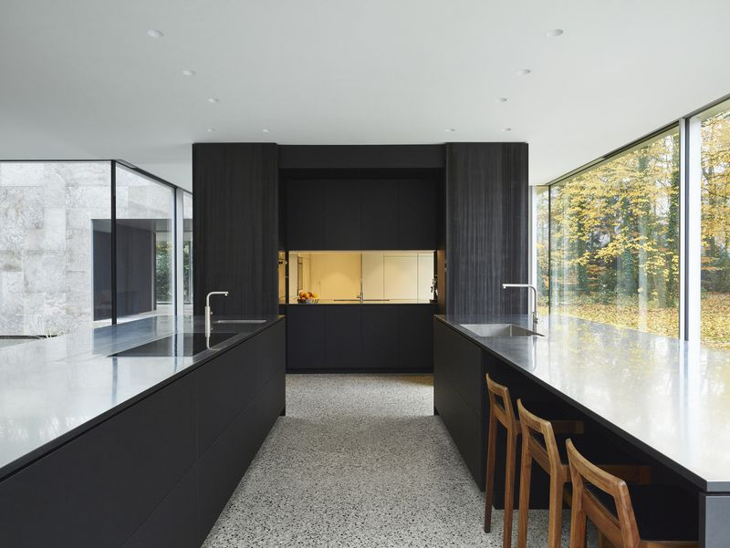 Open plan kitchen with two islands and a black cabinet in the back.