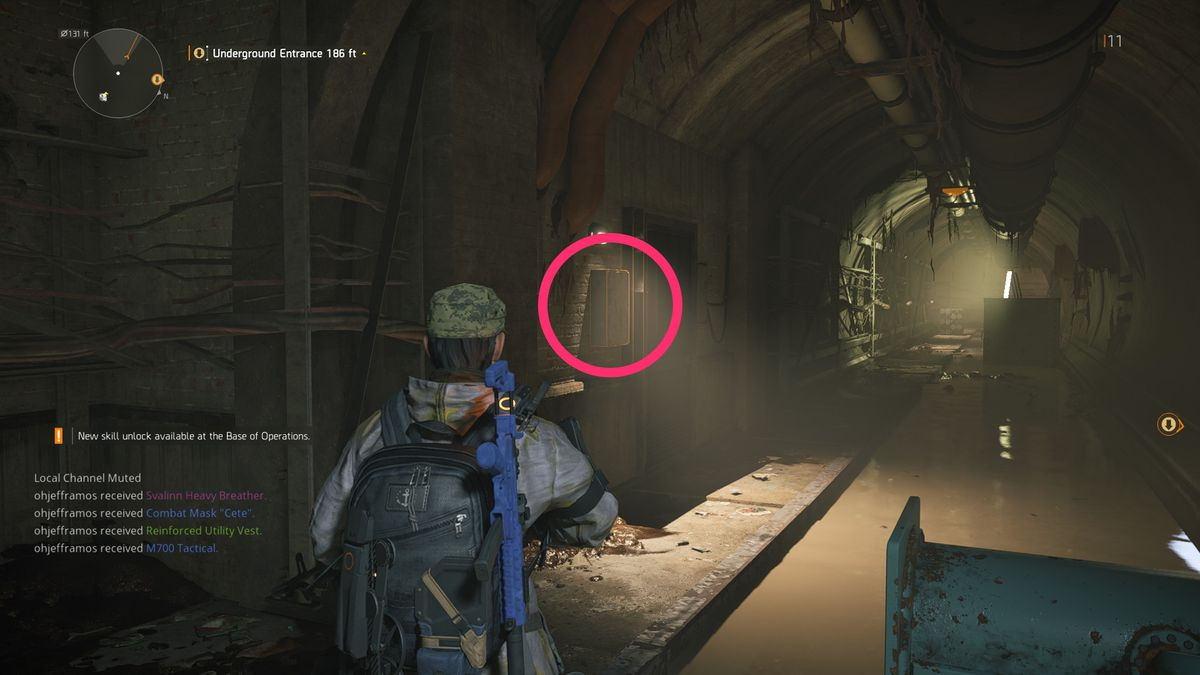 A soldier stares at a glowing orange box in The Division 2