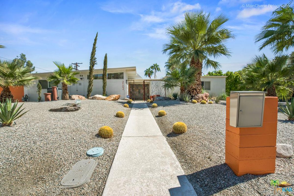 Desert landscaping makes up front yard of this single-story home with slightly sloping roof and iron gates marking the entrance.