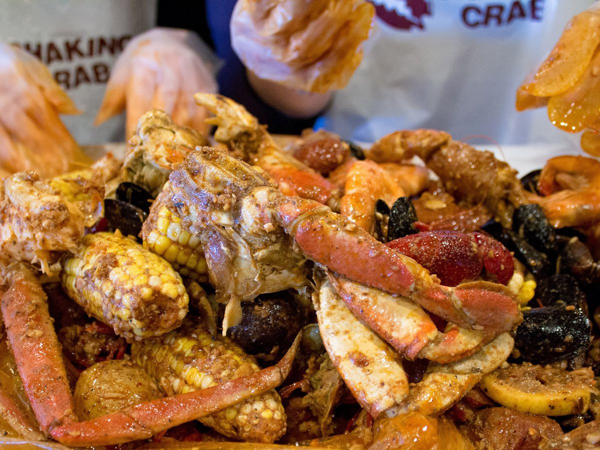 A mound of seafood and corn in front of two people.