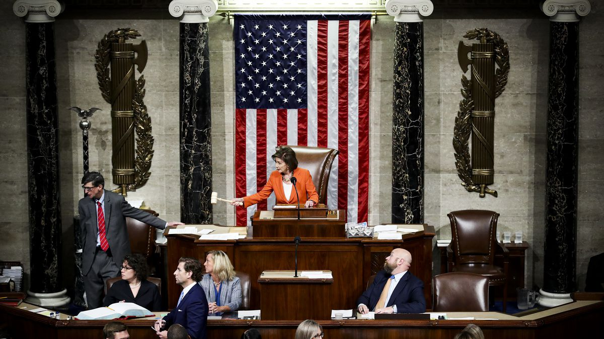 Speaker of the House Nancy Pelosi seated in the chair at the top of the House of Representatives with the American flag behind her and her fellow Representatives seated below.