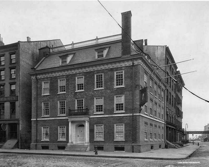 A large apartment building. The building has red bricks and on the lower level is a historic tavern with a large entryway.