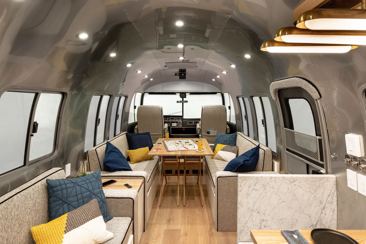 The front cabin of the Airstream features a living room with couches and a white oak table.