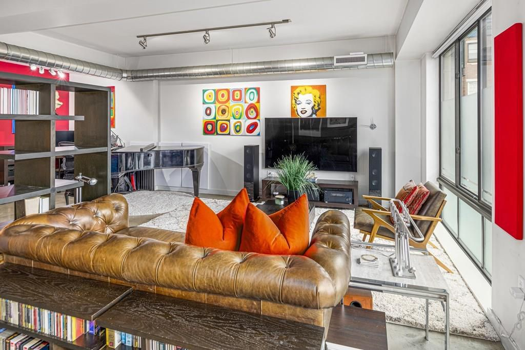 A large living room with a sectional couch facing a TV, and there is a set of windows on one side and.a set of shelves on the other.