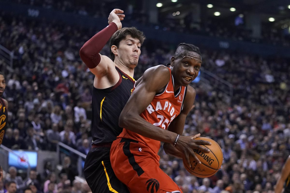 Toronto Raptors forward Chris Boucher tries to control the ball against Cleveland Cavaliers forward Cedi Osman during the first half at Scotiabank Arena.