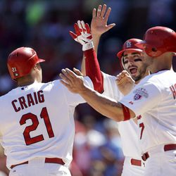 St. Louis Cardinals' Allen Craig, left, is congratulated by teammates Matt Carpenter, center, and Matt Holliday after hitting a three-run home run during the first inning of a baseball game against the Houston Astros Thursday, Sept. 20, 2012, in St. Louis.