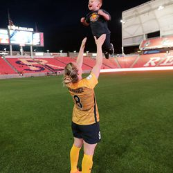 Utah Royals FC forward Amy Rodriguez (8) tosses her son Luke into the air after a match against the Orlando Pride at Rio Tinto Stadium in Sandy on Wednesday, May 9, 2018.