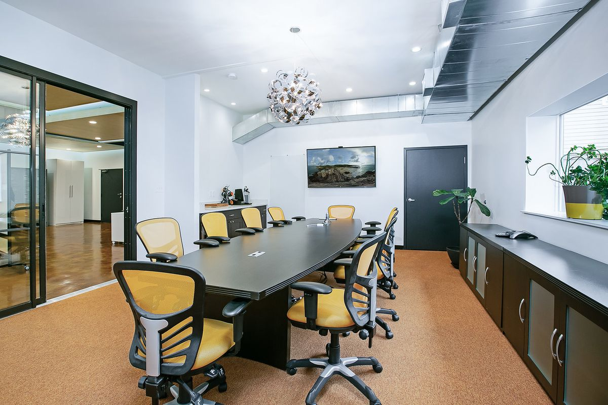 A conference table sits in a room with glass doors, duct work, plants and a silver contemporary light fixture.
