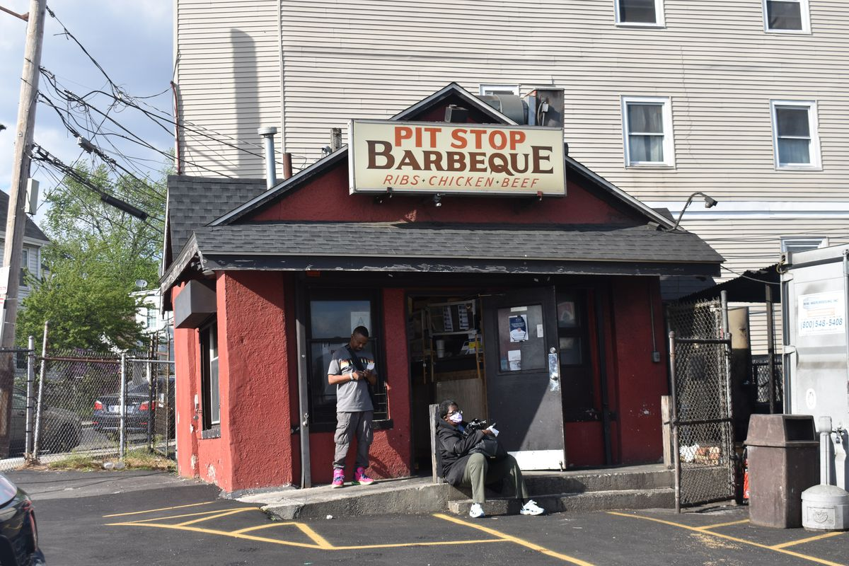Exterior of a small red building with signage that reads Pit Stop Barbeque. Two people wait outside.