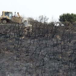 An excavator plows a new road for the power company to access when they install new power lines above Bybee Road in Ogden on Wednesday, Sept. 6, 2017. At least six structures, including multiple homes, have been destroyed after a brush fire erupted in Weber Canyon Tuesday morning.