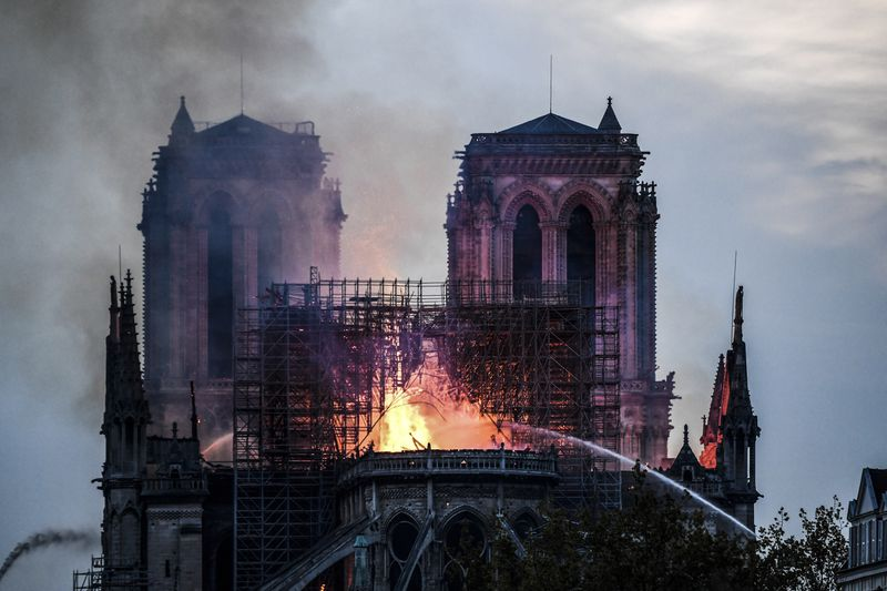 Firefighters douse flames and smoke billowing from the roof at Notre Dame Cathedral.