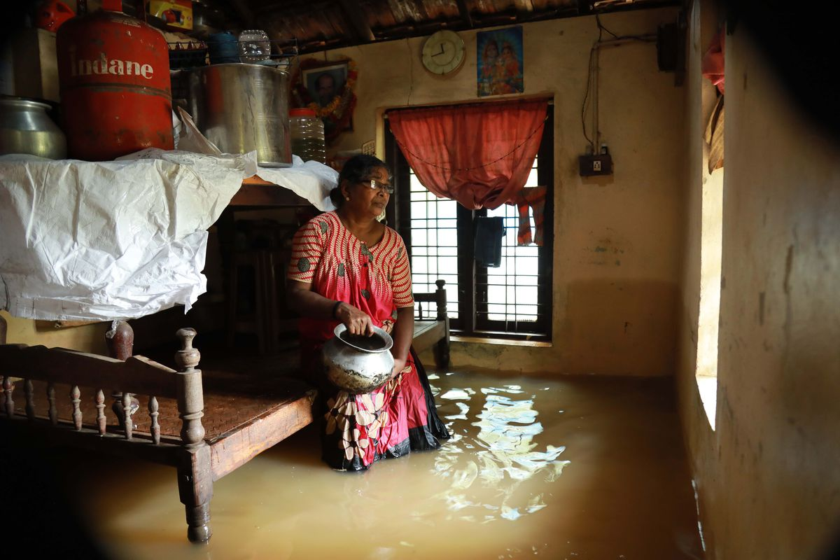An Indian woman sits inside her houses immersed in flood waters in Ernakulam district of Kochi, in the Indian state of Kerala on August 10, 2018.