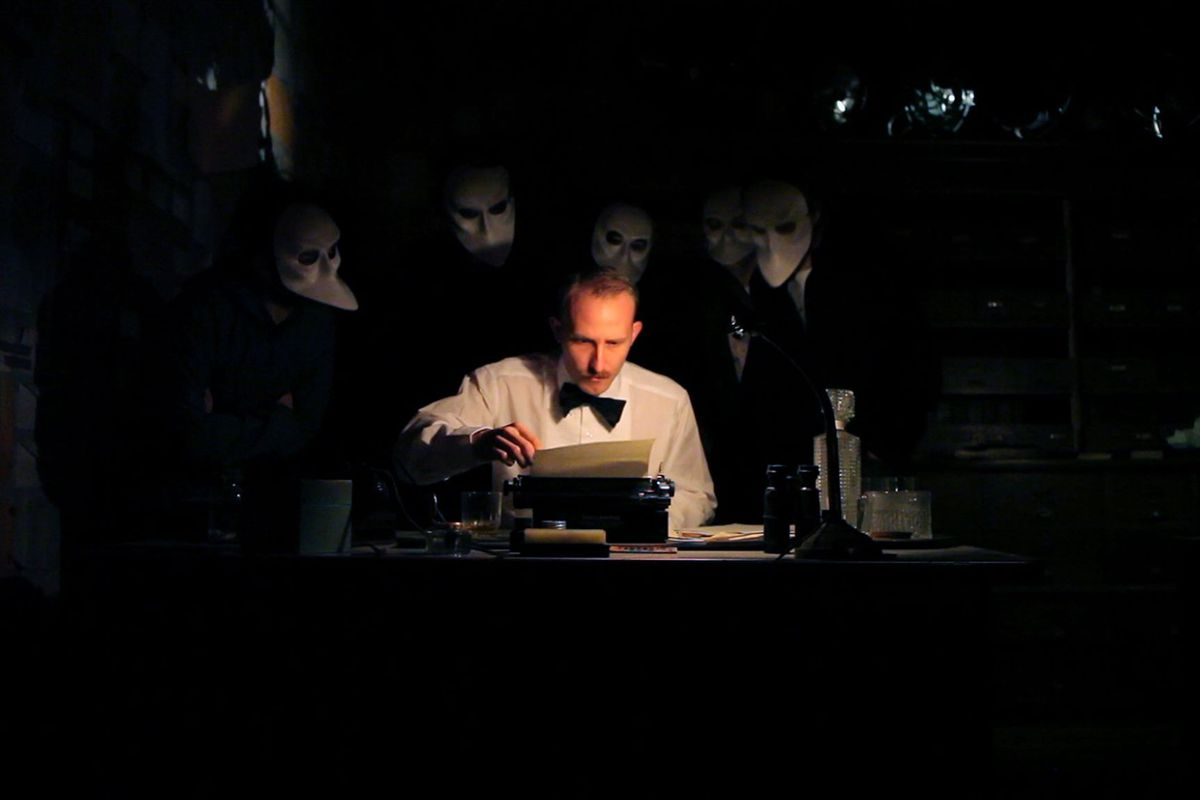 Masked viewers watch an actor at a typewriter during a performance of Sleep No More