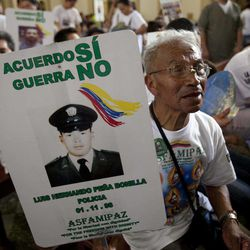 Relatives of police and soldiers held hostage by rebels of Revolutionary Armed Forces of Colombia, FARC, hold up signs with pictures of kidnapped love ones during a mass in Villavicencio, Colombia, Sunday, April 1, 2012.  The Revolutionary Armed Forces of Colombia, FARC, the country's largest rebel group plans to release its last 10 police and military prisoners allegedly in two groups on April 2 and April 4.