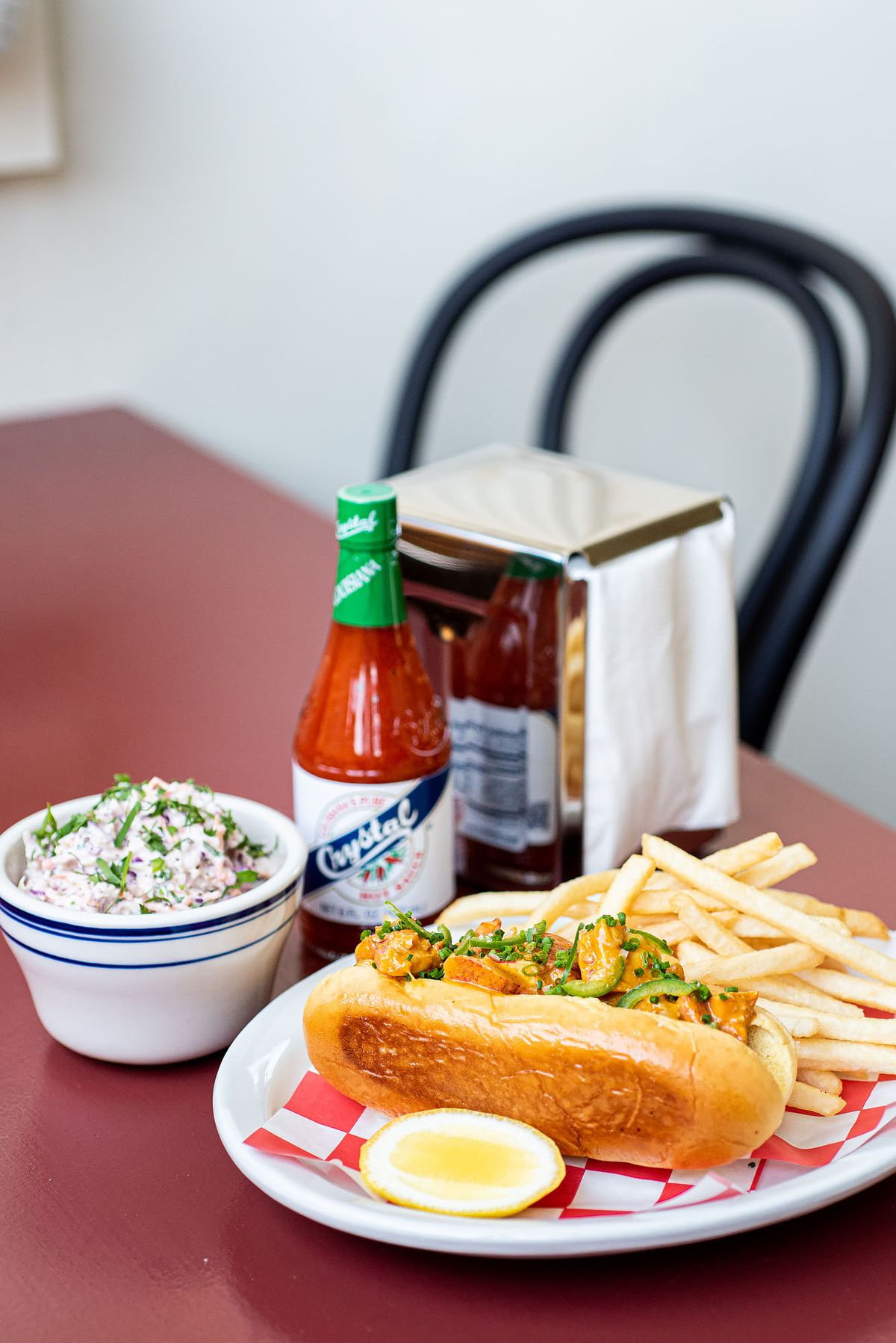 Lobster roll and fries on a plate with hot sauce in background.