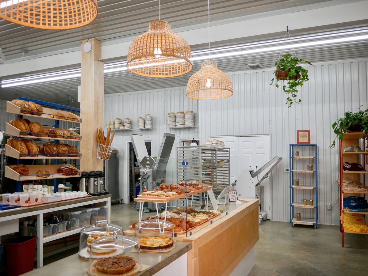 A bakery counter with displays of pastries with shelves of bread in the back
